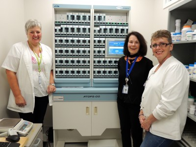 Pharmacy staff (l. to r.) Cindy Kerkhof, Mary Whyte and Karen Schipper have worked tirelessly to help implement new EMR technologies including this PACMED machine, which packages, labels and barcodes individual patient medication doses.