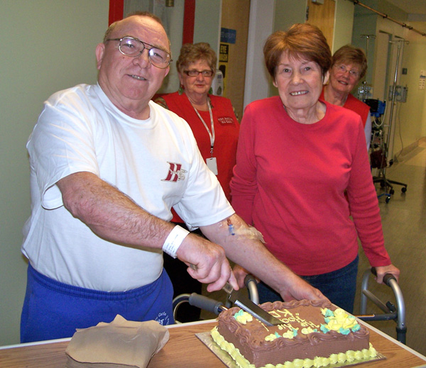 The first two hip replacement patients at KDH: Bryne Nuttall (left) and Maureen Mindach cut a celebratory cake while KDH Auxiliary volunteers Catherine Brunton (left) and Louise Tallman look on
